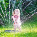 little girl sprinkler backyard