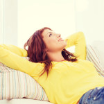 contented woman sofa yellow shirt