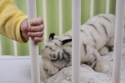 baby in crib hand holding crib bars