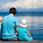 Dad sitting with children on dock by water