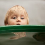 little boy and rain barrel