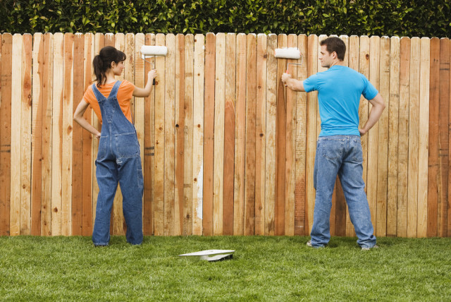 couple painting fence