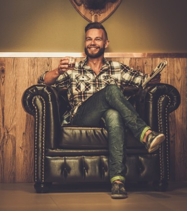 man in leather chair with drink