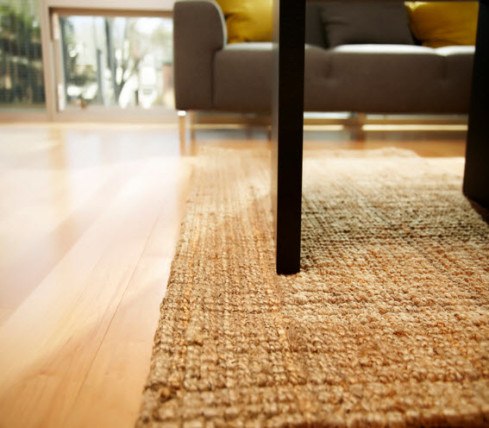 jute area rug and light colored wood flooring