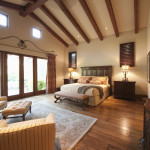 spacious bedroom area rug wood flooring furniture