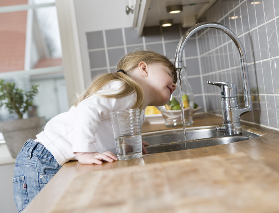 girl drinking from kitchen sink