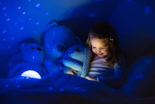 little girl reading by night light