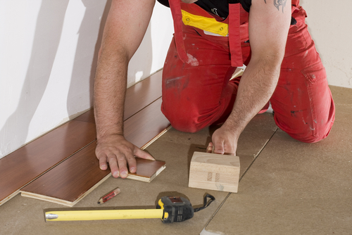 worker installs a hardwood floor